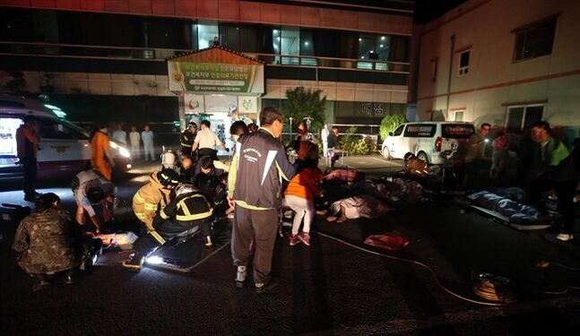 Firefighters rescue victims at a hospital in Jangseong, South Korea, Wednesday, May 28, 2014. South Korean officials said 20 patients and one nurse died in a fire at a hospital in the southwestern city of Jangseong. (AP Photo/Yonhap, Hyung Min-woo) KOREA OUT