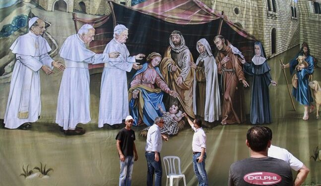 Palestinian workers hang up a giant banner featuring Jesus' birth with former Popes, from left, Pope Paul VI, John Paul II and Pope Benedict XVI at Manger Square outside the Church of the Nativity, revered as the site of Jesus' birth, in the West Bank city of Bethlehem, Friday, May 23, 2014. Pope Francis' trip to the Middle East offers a host of symbolically important (and potentially problematic) moments, from the gifts he'll receive to the venues he'll visit and the words he will pronounce. (AP Photo/Nasser Shiyoukhi)