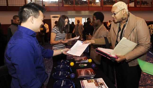 FILE - In this April 23, 2014 file photo, Luke Gill, left, of Quicken Loans, talks with job candidate Jasmine Boykins at a job fair at the Matrix Center in Detroit. The Conference Board releases the Consumer Confidence Index for April on Tuesday, April 29, 2014. (AP Photo/The Detroit News, David Coates, File)