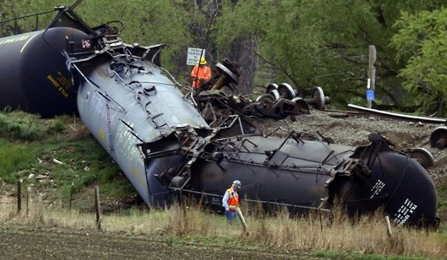 Clean up crews examine the damage at a train car derailment southwest of LaSalle, Colo. on Friday, May 9, 2014. The train, loaded in Windsor with Niobrara crude bound for New York, derailed around 8 a.m. according to Union Pacific Spokesman Mark Davis. Officials found one car of the 100-car train was leaking. (AP Photo/The Greeley Tribune, Joshua Polson)