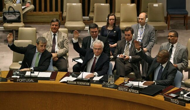 FILE - Members of the United Nations Security Council, including Russia's U.N. Ambassador Vitaly Churkin, foreground second from left, raise their hands in this April 14, 2012 file photo taken at U.N. headquarters. The U.N. Security Council faces a dramatic vote Thursday May 22, 2014 on referring the Syrian crisis to the International Criminal Court for investigation of possible war crimes, with dozens of countries signing on to embarrass Russia which vowed to kill the measure that demands a path to justice. (AP Photo/Craig Ruttle, File)
