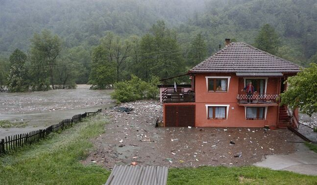 Bosnian people wave from a house near Zepce, 120 kms north of Sarajevo, Thursday May 15, 2014. Heavy rainfall caused the river Bosna to flood surrounding areas causing power cuts and road blockades in some suburban and rural areas. (AP Photo/Amel Emric)