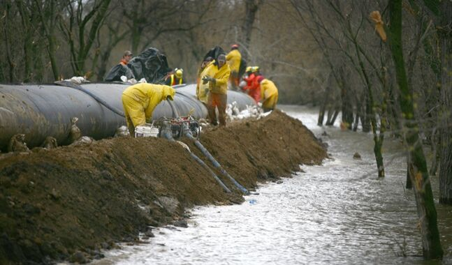 City crews, along with firefighters with Manitoba Conservation, work at topping up the the southern dike with aqua dams during Brandon's 2011 spring flood.