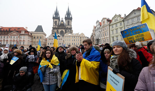 "Protesters with Ukrainian flags and placards gather at the Old Town square in Prague, Czech Republic, on Sunday to support ongoing protests in Ukraine. Three protesters have died in the past week and various local members of parliament have condemned the Ukrainian government's actions toward protesters, calling them ""unwarranted"" and ""unnecessary."""