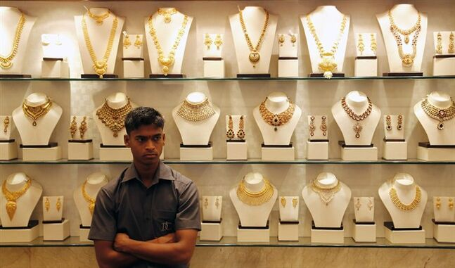 In this Friday, Dec. 6, 2013 photo, an Indian salesman stands by a counter at a gold jewelry shop in Mumbai, India. Gold is India's second-biggest import behind oil, and purchases have soared in recent years as rising incomes from a decade of economic growth sent Indian consumers on a buying streak. The problem is that the greater buying of the precious metal has dealt a blow to India's economy by increasing the flow of money out of country compared to inflows. As a result, the current account deficit rose to a historic high of 4.8 percent of India's gross domestic product in the fiscal year that ended in March. (AP Photo/Rajanish Kakade)