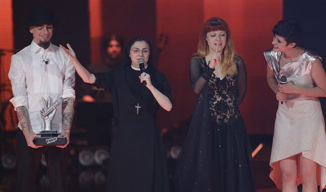 Sister Cristina Scuccia, second from left, recites the prayer 'Our Father' on the stage after winning the final of the Italian version of the TV talent show