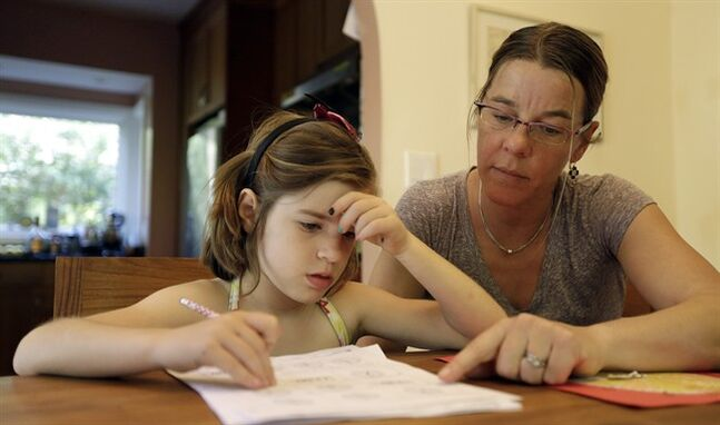 "Stacey Jacobson-Francis, right, works on math homework with her 6 year old daughter Luci Wednesday, May 14, 2014, at their home in Berkeley, Calif. As schools around the U.S. implement national Common Core learning standards, parents trying to help their kids with math homework say that adding, subtracting, multiplying and dividing has become as complicated as calculus. Stacey Jacobson-Francis, 41, of Berkeley, California, said her daughter's homework requires her to know four different ways to add. ""That is way too much to ask of a first grader. She can't remember them all, and I don't know them all, so we just do the best that we can,"" she said. (AP Photo)"