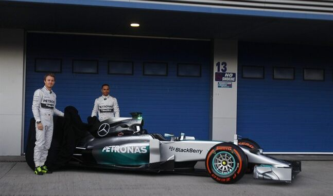 Mercedes GP drivers Nico Rosberg of Germany, left, and Lewis Hamilton of Great Britain, right, pose for photos during the launch of their new Mercedes W05 Formula One car at the Circuito de Jerez on Tuesday, Jan. 28, 2014, in Jerez de la Frontera, Spain. (AP Photo/Miguel Angel Morenatti)