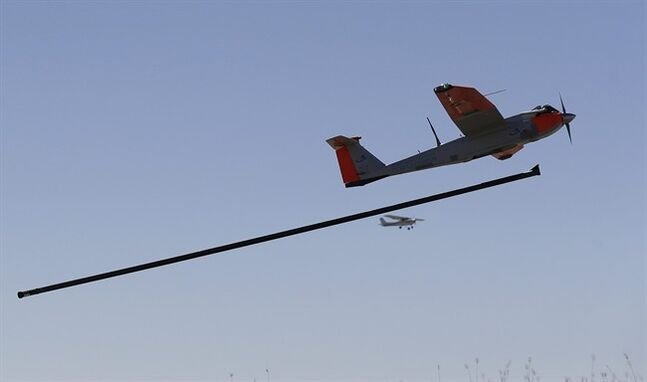 FILE - This Jan. 15, 2014, file photo shows a test drone as it is is launched by catapult as a trail plane follows on a ranch near Sarita, Texas. Model aircraft hobbyists, research universities and commercial drone operators and investors have filed lawsuits challenging a government directive that they say imposes tough new limits on the use of model aircraft and broadens a ban on commercial drone flights. (AP Photo/Eric Gay, File)