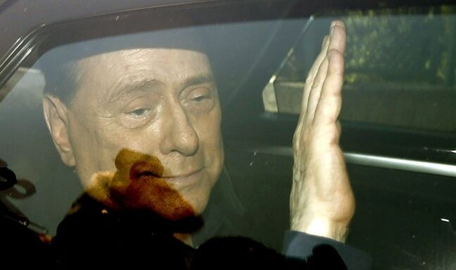 ALTERNATIVE VERSION OF XLB101-- Italy's former Premier Silvio Berlusconi waves as he leaves the 'Sacra Famiglia' institute in Cesano Boscone, Italy, Friday, July 18, 2014. An Italian appeals court has acquitted former Premier Silvio Berlusconi in a sex-for-hire case. The court's decision Friday also throws out his seven-year-prison sentence and lifetime ban on holding political office that were given to him by a lower court when it convicted him last year. Berlusconi had been accused of of paying for sex with an underage prostitute and then using his influence to cover it up. (AP Photo/Luca Bruno)