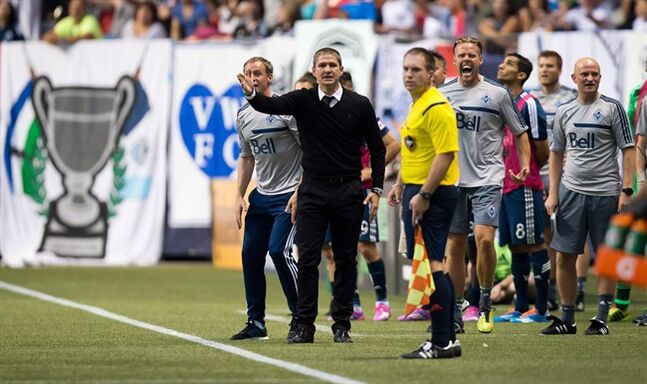 Vancouver Whitecaps' head coach Carl Robinson, centre, and others on the bench react to a no goal call during the second half of an MLS soccer game against Chivas USA in Vancouver, B.C., on Saturday July 12, 2014. The Whitecaps's inability to close out games has coach Robinson feeling a bit ill-tempered. THE CANADIAN PRESS/Darryl Dyck