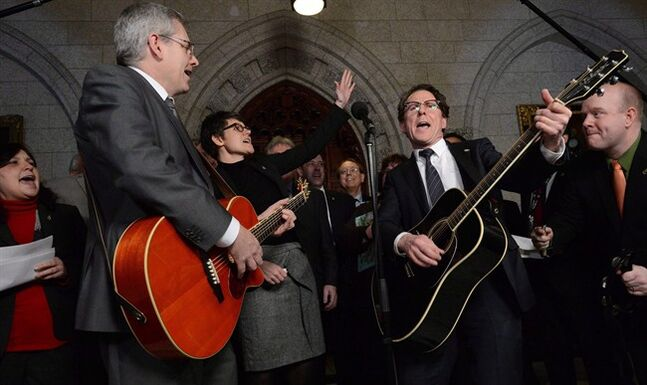 NDP MPs Charlie Angus, Megan Leslie and Andrew Cash are joined by fellow NDP MPs performing a Stompin' Tom song in the foyer of the House of Commons on Parliament Hill in Ottawa on Thursday March 7, 2013. Ottawa has effectively eliminated a fee charged to international musicians that critics complained was deterring acts from abroad from playing in Canadian bars, pubs and restaurants. THE CANADIAN PRESS/Sean Kilpatrick