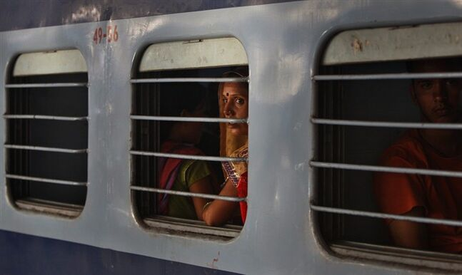 An Indian woman looks out through the window of a train as it leaves a railway station in Jammu, India, Monday, July 7, 2014. India on Tuesday is expected to announce the budget for the national railways system, which is one of the world's largest and serves 23 million passengers a day. (AP Photo/Channi Anand)