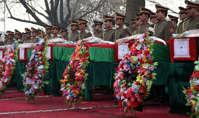 Members of the Honor Guard stand at attention near the caskets of victims of Afghan national army soldiers during a funeral ceremony in Kabul, Afghanistan, Monday, Feb. 24, 2014. Afghanistan's defense minister has paid tribute at a somber ceremony to 21 soldiers killed in the deadliest single incident for the Afghan army in at least a year. The soldiers were killed Sunday when hundreds of heavily armed Taliban insurgents attacked a remote Army outpost in eastern Afghanistan's Kunar Province. (AP Photo/Rahmat Gul)