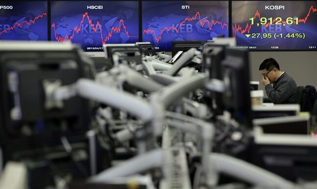 FILE - In this Monday, Jan. 27, 2014, file photo, a currency trader adjusts his glasses near the screens showing the Korea Composite Stock Price Index (KOSPI) at the foreign exchange dealing room of the Korea Exchange Bank headquarters in Seoul, South Korea. A global sell-off in stocks this year has left many small investors more puzzled than panicked and unsure how to act. Ordinary investors around the world were on edge even before signs of a slowdown in China and plunging emerging-market currencies sent stocks tumbling earlier this past week. Stocks had soared by double-digit percentages in countries like the United States, Japan and France in 2013, raising fears that they had climbed too fast and were due to drop.(AP Photo/Lee Jin-man, File)