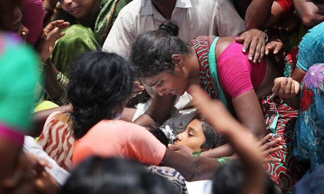 EDS NOTE GRAPHIC CONTENT- An unidentified woman cries by the body of a victim of an accident in Medak district in the southern Indian state of Telangana, Thursday, July 24, 2014. Twelve children were killed Thursday when a train crashed into a school bus at an unmanned railroad crossing in southern India, police said. There are hundreds of unmanned crossings across the country, especially in remote areas. (AP Photo/Mahesh Kumar A.)