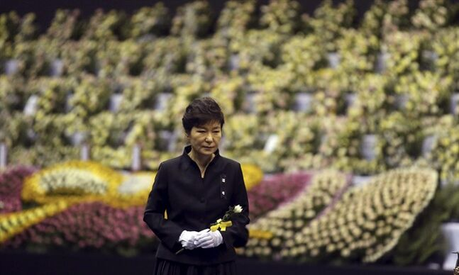 FILE - In this April 29, 2014 file photo, South Korean President Park Geun-hye pays tribute to the victims of the sunken ferry Sewol at a group memorial altar in Ansan, south of Seoul, South Korea. Park replaced seven Cabinet members Friday, June 13 in an apparent bid to win back sagging public trust in her administration after April's ferry disaster, which left 304 people dead or missing. (AP Photo/Yonhap, File) KOREA OUT