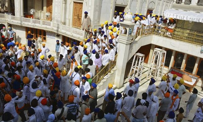 Members of a hardline Sikh group clash with guards of the Sikh's holiest shrine, the Golden Temple, in Amritsar, India, Friday, June 6, 2014. Half a dozen people were wounded Friday as members of a Sikh group brandishing swords and wooden sticks clashed with guards at the shrine, an official said. The clash occurred during a ceremony marking the anniversary of the storming of the shrine by the Indian army in June 1984 in the northern city of Amritsar, said Kiran Jyoti Kaur, a Golden Temple management spokeswoman. (AP Photo Prabhjot Gill)