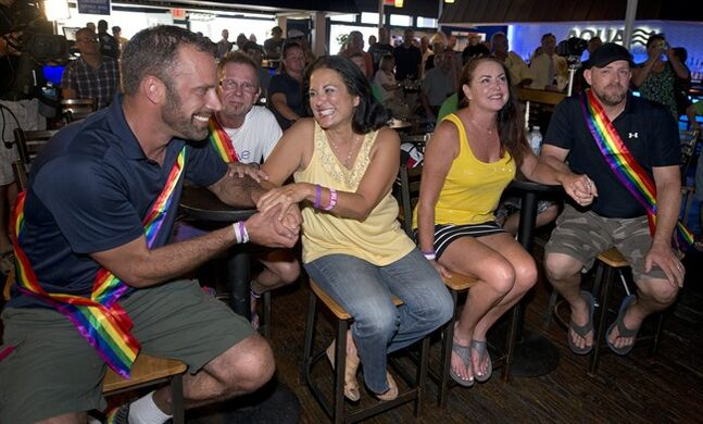 In this photo provided by the Florida Keys News Bureau, Aaron Huntsman, left, and and his partner William Lee Jones, right, listen to a speech with their attorneys Bernadette Restivo, second from left, and Jessica Reilly, third from left, Thursday, July 17, 2014, in Key West, Fla. Jones and Hunstman and about 100 other people marked a Florida Keys judge's ruling overturning Florida's ban on same-sex marriage on Thursday after a legal challenge. (AP Photo/Florida Keys News Bureau, Andy Newman)