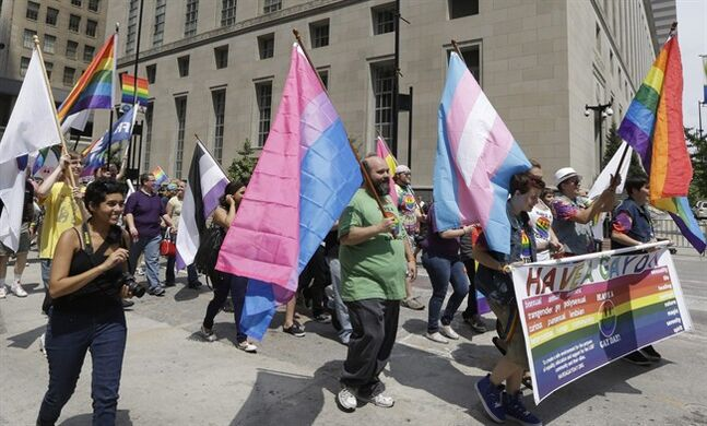 Gay marriage supporters around the Potter Stewart United States Courthouse Wednesday, Aug. 6, 2014, after holding a rally on Fountain Square in Cincinnati. Three judges of the 6th U.S. Circuit Court of Appeals in Cincinnati are set to hear arguments Wednesday in six gay marriage fights from four states, Kentucky, Michigan, Ohio and Tennessee. (AP Photo/Al Behrman)