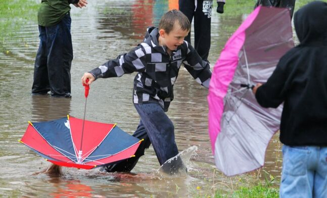 Some children enjoy the excess water created by the weekend's heavy rainfall at Crocus Plains school on Sunday.