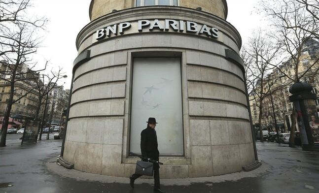 FILE - In this Feb. 5, 2013 file photo, a man walks past the French bank BNP Paribas headquarters in Paris. French economy minister Arnaud Montebourg on Monday, June 23, 2014 is urging U.S. authorities to be