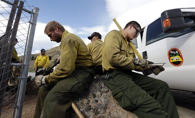 Firefighters Alex Keller, left, and Jacey Mesteth sharpen their tools as they wait to be deployed to a fire line Saturday, July 19, 2014, in Winthrop, Wash. A wind-driven, lightning-caused wildfire racing through rural north-central Washington destroyed about 100 homes Thursday and Friday, leaving behind solitary brick chimneys and burned-out automobiles as it blackened hundreds of square miles in the scenic Methow Valley northeast of Seattle. (AP Photo/Elaine Thompson)