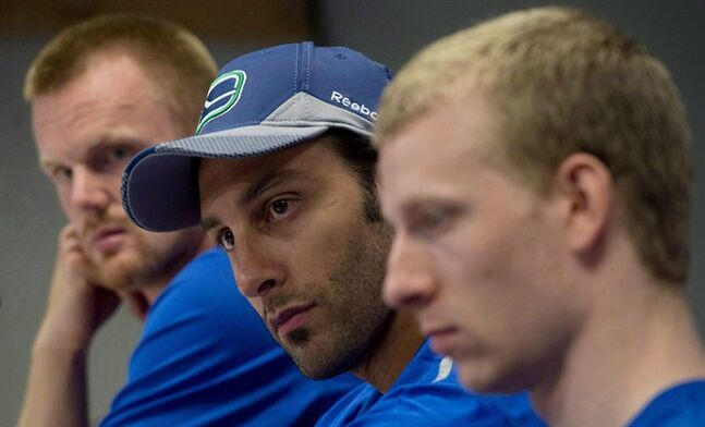 Vancouver Canucks Daniel Sedin, left to right, goaltender Roberto Luongo and Jannik Hansen attend a media availability at Rogers Arena in Vancouver, B.C. Wednesday, Sept, 11, 2013. Luongo won't have any family joining him next month when he suits up for Canada at the Winter Olympics.The same goes for Sweden's Daniel Sedin. THE CANADIAN PRESS/Jonathan Hayward