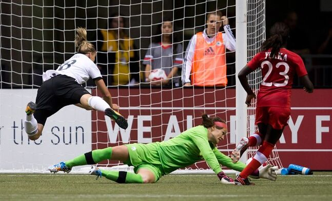 Germany's Alexandra Popp, left, jumps to avoid a collision as Canada's goalkeeper Erin McLeod, centre, makes the save while Sura Yekka defends during the second half of an international women's soccer game in Vancouver, B.C., on Wednesday June 18, 2014. THE CANADIAN PRESS/Darryl Dyck