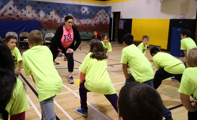 Riverview School physical education teacher Jen Thomson leads students in a running warm-up.