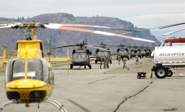 Washington National Guard Blackhawk helicopters are lined up near other aircraft at the airport in Omak, Wash. on Thursday, July 24, 2014. The Washington National Guard is helping fight wildfires in Washington state with four Blackhawks and two Chinook helicopters. (AP Photo)