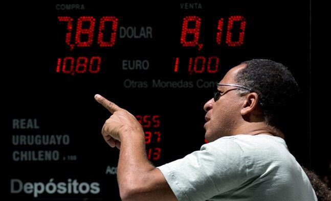 A man points forward as he passes in front of a board displaying going rates of U.S. dollars at a foreign exchange business in Buenos Aires, Argentina, Monday, Jan. 27, 2014. The Argentine government announced Friday it was relaxing restrictions on the purchase of U.S. dollars. The measure would start taking effect Monday, allowing Argentines to buy pesos for personal savings, reversing a 2012 restriction. (AP Photo/Natacha Pisarenko)