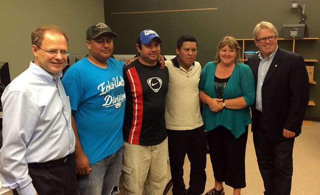 Winnipeg North MP Kevin Lamoureux (left) and Cape Breton-Canso MP Rodger Cuzner (right) pose for a photo with temporary foreign workers during their stop in Brandon on Thursday.