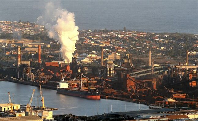 In this July 2, 2014 photo, smoke billows out of a chiming chimney stack of steel works factories in Port Kembla 86 kilometers (53 miles) south of Sydney. The Senate is expected to vote as early as Monday, July 7, 2014, to repeal an unpopular, two-year-old tax charged to around 300 of the country's biggest carbon polluters. (AP Photo/Rob Griffith)