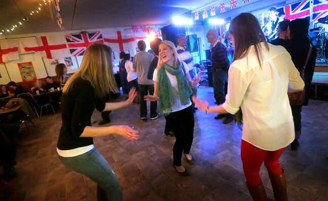 Friends Alana Martin, Jodi Mangin and Rinautta McConnell dance to the sounds of Until Red, which played a collection of British pop songs, at the English pavilion during the Lieutenant Governor's Winter Festival on Saturday night.