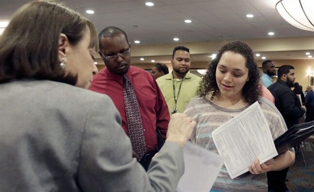FILE - In this April 28, 2014 file photo, Natalie Silverstein, of the Broward County Transportation Department, left, explains the job openings at the County to job seeker Janely Ramos, right, during a job fair in Fort Lauderdale, Fla. The Labor Department releases job openings and labor turnover survey for March on Friday, May 9, 2014. (AP Photo/Alan Diaz, File)