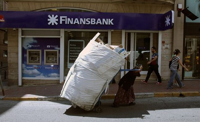 An elderly scrap collector pulls her trolley in front of a Turkish bank in Istanbul, June 4, 2013. THE CANADIAN PRESS/AP, Thanassis Stavrakis