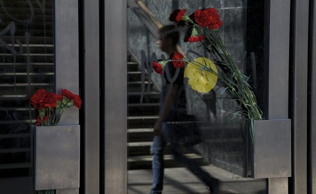 Flowers are fixed on doors as an unidentified man walks past an entrance of Slavaynsky boulevard subway station, in Moscow, Russia, on Wednesday, July 16, 2014. A rush-hour subway train derailed in Moscow Tuesday, killing 20 people and injuring at least 150, emergency officials said. The cause of the derailment is being investigated. (AP Photo/Ivan Sekretarev)