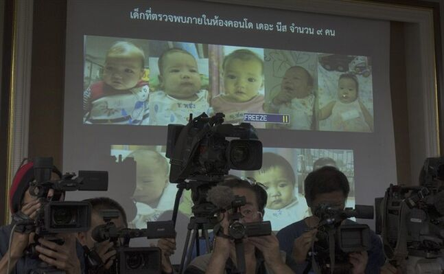 "In this Tuesday, Aug. 12, 2014 photo, Thai police display pictures of surrogate babies born to a Japanese man who is at the center of a surrogacy scandal during a press conference at the police headquarters in Chonburi, Thailand. Interpol said Friday it has launched a multinational investigation into what Thailand has dubbed the ""Baby Factory"" case: the 24-year-old Japanese businessman who has 16 surrogate babies and an alleged desire to father hundreds more. Police raided a Bangkok condominium earlier this month and found nine babies and nine nannies living in a few unfurnished rooms filled with baby bottles, bouncy chairs, play pens and diapers. They have since identified Mitsutoki Shigeta as the father of those babies - and seven others. (AP Photo/Sakchai Lalit)"