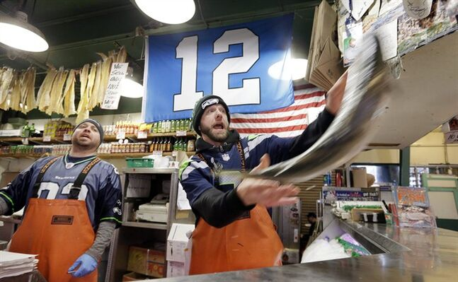 Fish monger Justin Hall, right, launches a salmon as Scott Smith looks on as the pair wear Seattle Seahawks' jerseys and work beneath a