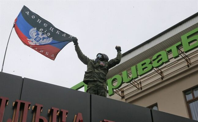 A masked pro-Russian activist places a self-proclaimed 'Donetsk Republic' flag over the office of a