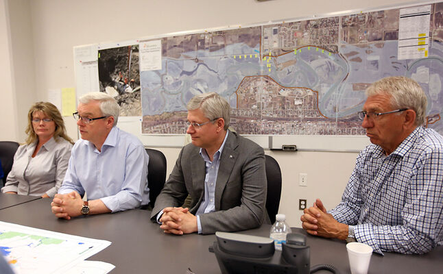 Saint Boniface Conservative MP Shelly Glover, from left, Premier Greg Selinger, Prime Minister Stephen Harper and Brandon-Souris Conservative MP Larry Maguire listen to a flood briefing at Brandon City Hall during a tour of the Assiniboine River flooding on July 6.