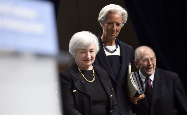 International Monetary Fund (IMF) Managing Director Christine Lagarde, center, walks with Federal Reserve Chair Janet Yellen, left, and former International Monetary Fund Managing Director Michel Camdessus, as they arrive for a lecture series at the IMF in Washington, Wednesday, July 2, 2014. Yellen said she doesn't see a need for the Fed to start raising interest rates to address the risk that extremely low rates could destabilize the financial system. (AP Photo/Susan Walsh)