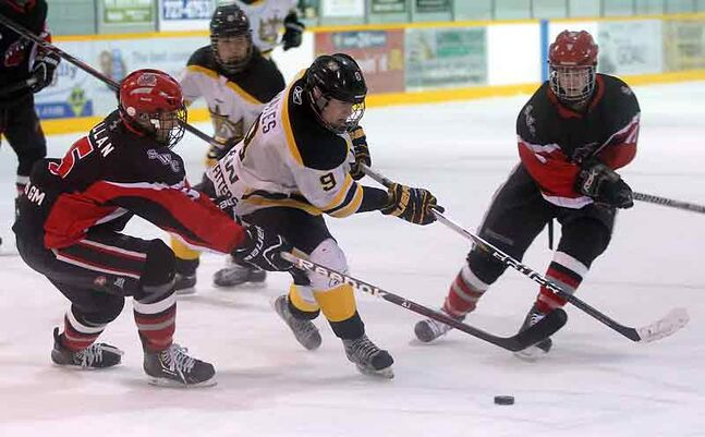 Wheat King Coltyn Bates gets past Southwest Cougars' Matthew Millan, left, during Saturday night's Manitoba AAA Midget hockey game at the Sportsplex. Brandon posted a 7-2 victory.