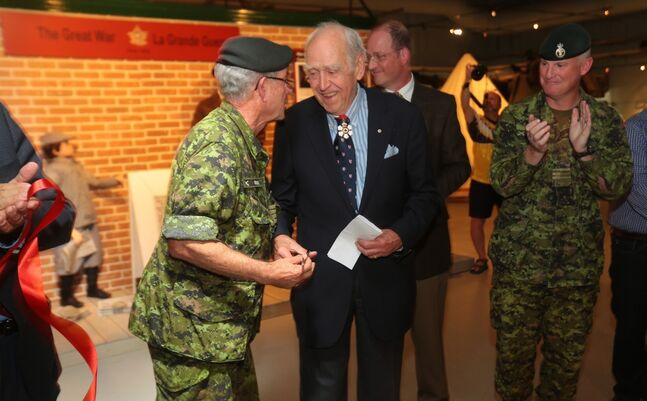 26th Field Regiment Honorary Col. Rick Felstead, left, shakes hands with Canadian film director, producer and writer Paul Almomd following the official ribbon cutting for the First World War exhibit with RAC Museum director Marc George and Base Commander Lt-Col. Stephen Joudrey at CFB Shilo on Monday.