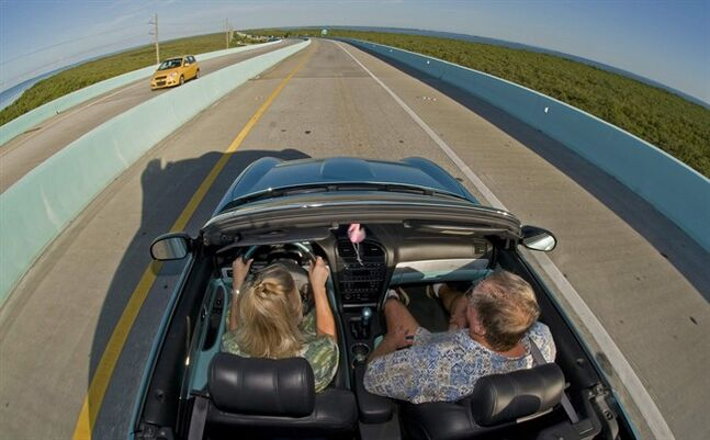 A couple rides in a convertible car, Wednesday, Sept. 28, 2011, near Key Largo, Fla., Canadians visiting Florida may be surprised to hear they now need an International Driving Permit to motor around the state. THE CANADIAN PRESS/AP-Florida Keys News Bureau, Andy Newman