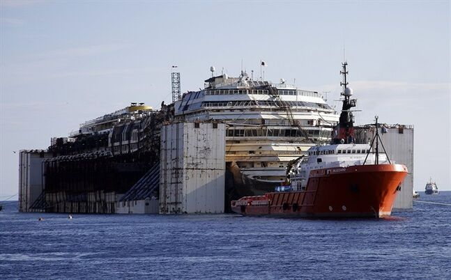 The Costa Concordia cruise wreck is maneuvered into position to be towed away from the tiny Tuscan island of Isola del Giglio, Italy, Wednesday, July 23, 2014. After more than two years since it slammed into a reef along the coastline of Isola del Giglio the wreck has begun its last journey, to the Italian port of Genoa, where it will be scrapped. 32 people died in the incident. (AP Photo/Gregorio Borgia)