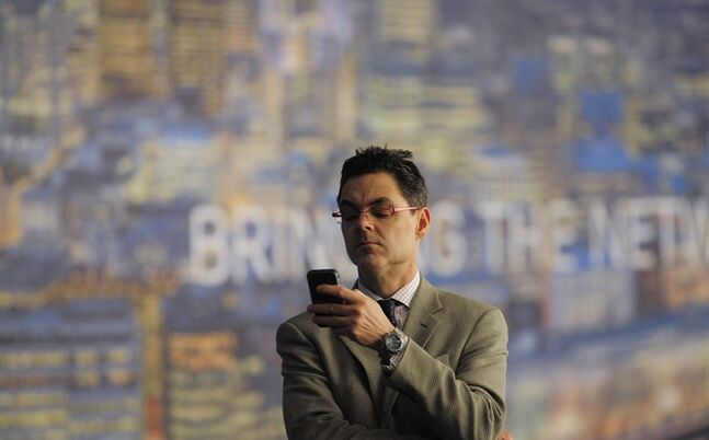 FILE - In this Wednesday, Feb. 27, 2013, file photo, a man checks his phone at the Mobile World Congress, the world's largest mobile phone trade show, in Barcelona, Spain. The U.S. wireless industry is in the midst of a shake-up, to stop subsidizing phones bought by its customers. That means customers can quickly get the new phones expected this week at the 2014 Mobile World Congress wireless show, which begins Monday, Feb. 24, 2014, in Barcelona, Spain. (AP Photo/Manu Fernandez, File)