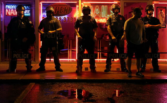 Police officers take up their positions in front of businesses on the main strip in Ferguson, Mo. on Saturday night. A curfew was to go into effect at midnight, but some defied it.
