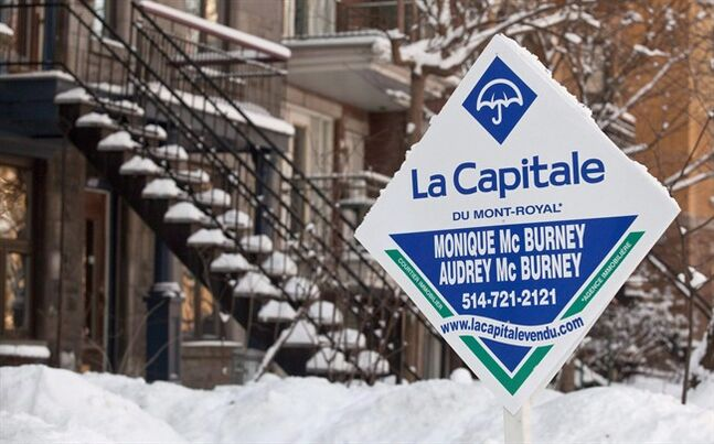 A real estate sign is seen in front of a Montreal home on January 17, 2011. THE CANADIAN PRESS/Paul Chiasson